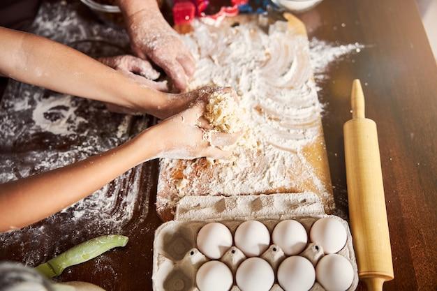 キッチンテーブルで生地を混ぜる経験豊富なパン屋