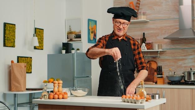 Fornaio esperto che sparge farina nella cucina di casa per la preparazione del cibo. chef anziano in pensione con bonete e grembiule che cosparge, setacciando setacciando gli ingredienti crudi a mano che cuoce pizza fatta in casa, pane.