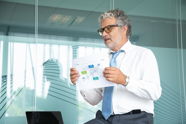 Experienced boss sitting and showing strategy plan