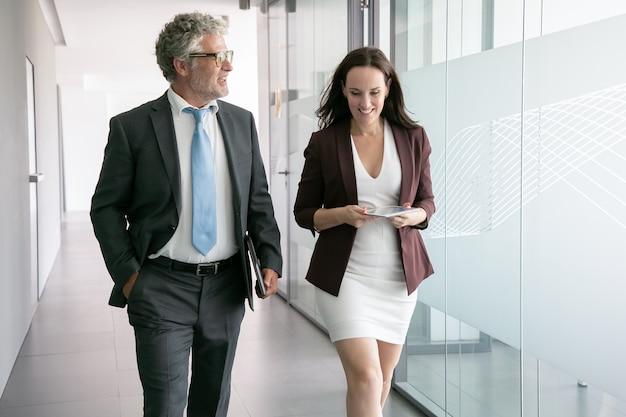 オフィスの廊下を歩いて話している経験豊富なビジネスマン