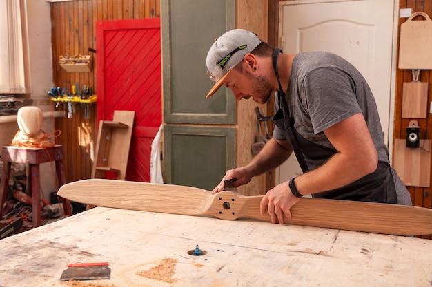 作業服を着た経験豊富な大工と木工ワークショップで働く小さな事業主、子供用ヘリコプターの研磨にサンドペーパーを使用