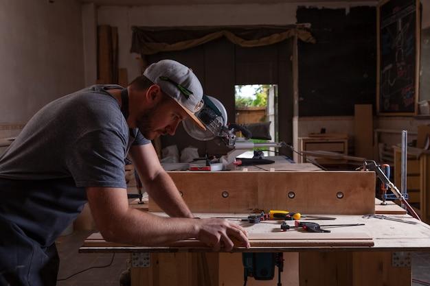 작업장에서 나무로 작업하는 작업복의 숙련 된 목수