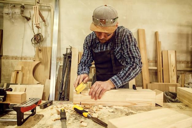 木工ワークショップで働く経験豊富な大工、作業台で巣箱を磨くためにサンドペーパーを使用
