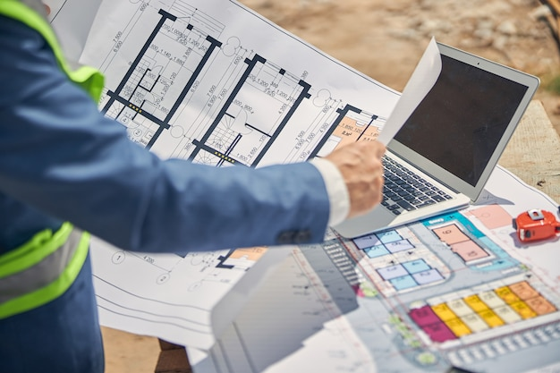 An experienced caucasian civil engineer examining the house plan in his hands