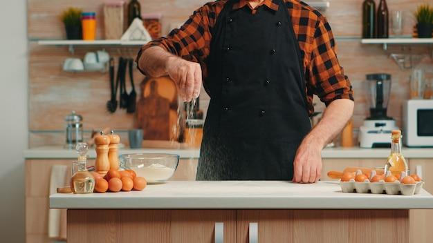 Chef fornaio esperto che utilizza farina di frumento spalmandola per la preparazione del cibo. uomo anziano in pensione con bonete e grembiule che spolvera setacciando gli ingredienti setacciando a mano la pizza e il pane fatti in casa