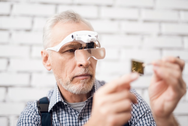 Experienced computer master examines microchip.