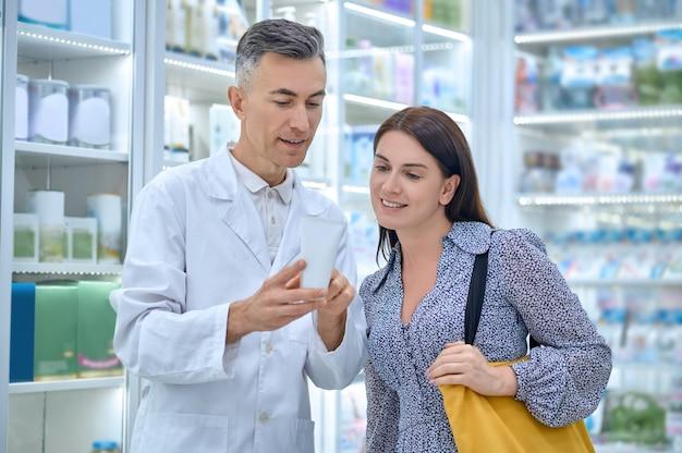 Опытный фармацевт-консультант, консультирующий клиента-женщину