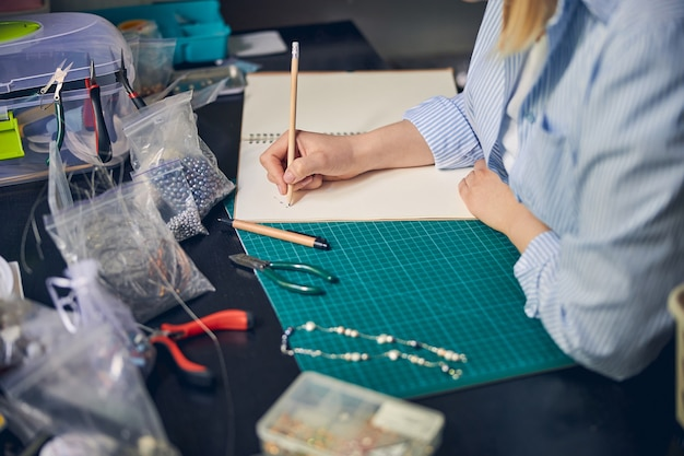 Опытный дизайнер рисует эскиз изделия колье, держа руки на столе.