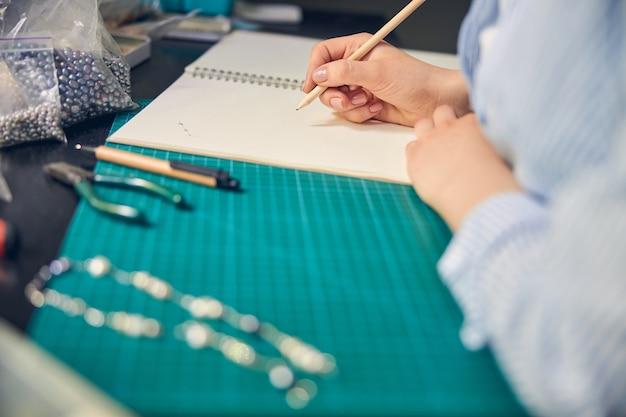 Опытный дизайнер работает над эскизом ожерелья, сидя за столиком в студии