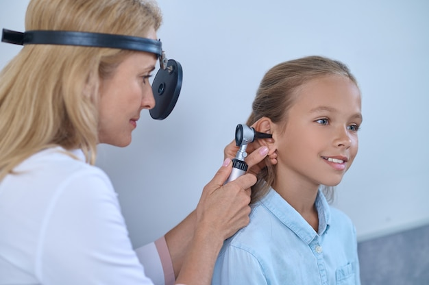 Experienced doctor inserting the auriscope into the patients auditory canal