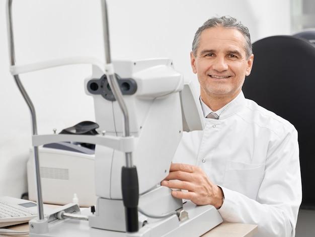 Опытный врач-офтальмолог позирует с щелевой лампой.