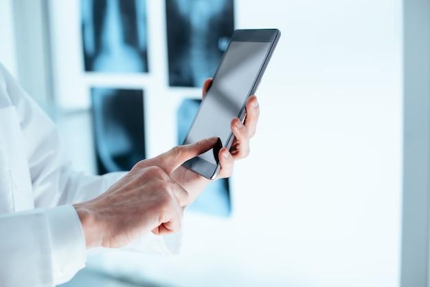 Опытный врач, использующий цифровой планшет для уточнения данных