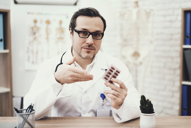 Experienced doctor with stethoscope and pack of tablets.