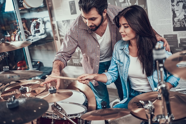 Experienced drummer teaches young girl playing drum set
