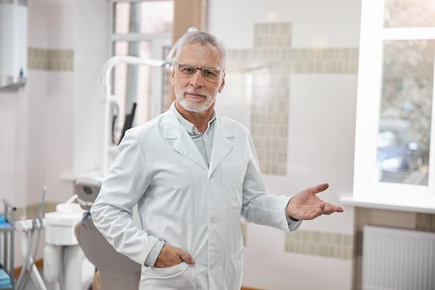 사무실에 서있는 동안 손을 내밀고있는 경험 많은 노인 치과 전문의