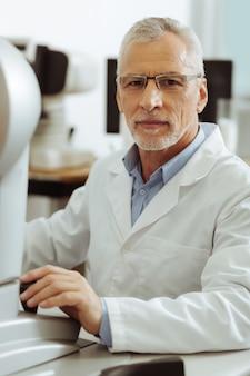 Опытный глазной врач. профессиональный опытный глазной врач в униформе сидит за столом