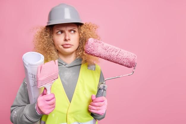 経験豊富な女性デコレータがペイントツールを保持し、不機嫌そうな真面目な表情で離れて制服を着て青写真を運び、保護作業服を着て屋内に立つ