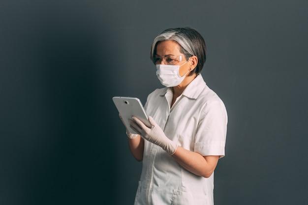 タブレットコンピューターを使用して経験豊富な女性医師。デジタルガジェットを扱う保護服で成熟した白人女性。医学概念の先端技術