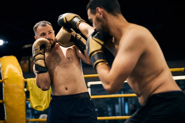 Experienced fighter parrying a blow to the head from his sparring partner