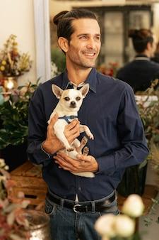 Опытный флорист держит собаку и улыбается