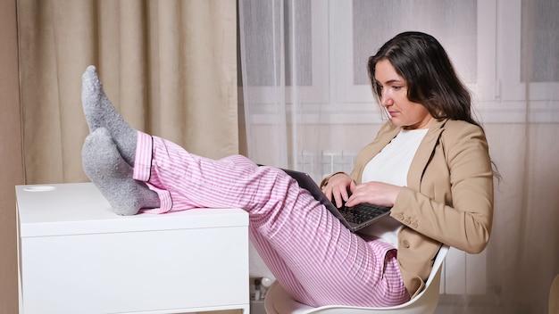 長い髪の経験豊富なフリーランサーが白い椅子に座ってテーブルに足を置き、自宅のパンデミック検疫でラップトップに膝を打ちます
