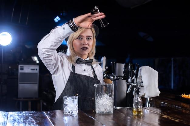 経験豊富な女の子のバーテンダーがナイトクラブでカクテルを作るショーを作ります