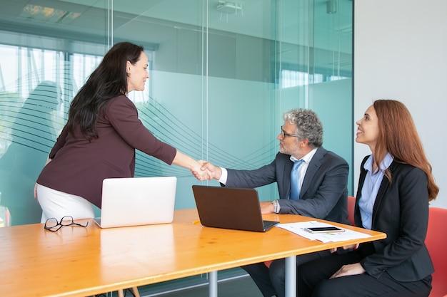 Опытный седой генеральный директор сидит и приветствует бизнесвумен