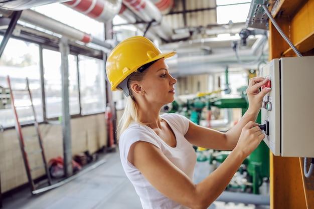 Опытная трудолюбивая независимая женщина в рабочей одежде со шлемом на голове стоит рядом с приборной панелью и регулирует настройки, стоя на тэц.