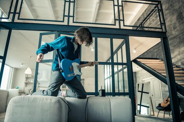 Опытный одухотворенный парень. сумасшедший длинноволосый парень играет на электронной гитаре в двухуровневой квартире