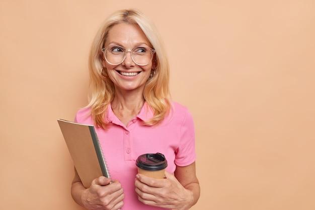 Tutor femminile intelligente esperta dà lezioni private bevande caffè da asporto tiene taccuini sorrisi indossa piacevolmente occhiali ottici maglietta rosa isolata sopra lo spazio della copia muro marrone