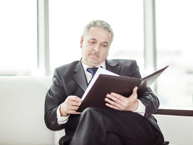 숙련 된 변호사가 새 계약 조건으로 문서를 검토합니다.