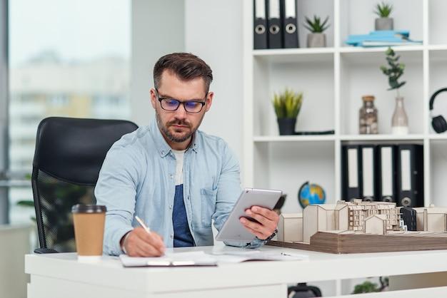 Опытный архитектор-мужчина в офисе осматривает проект жилого комплекса и производит расчеты.