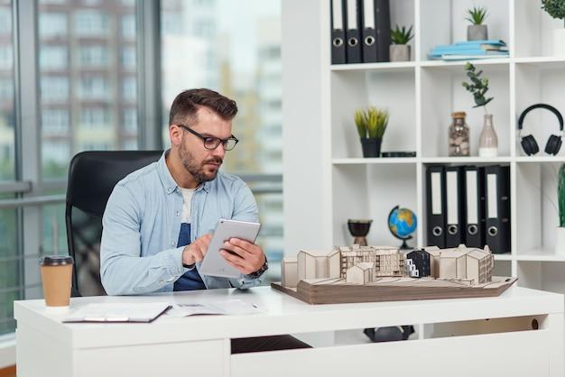 の経験豊富な男性建築家が集合住宅のプロジェクトを視察し、タブレットpcを使用して計算を行います。
