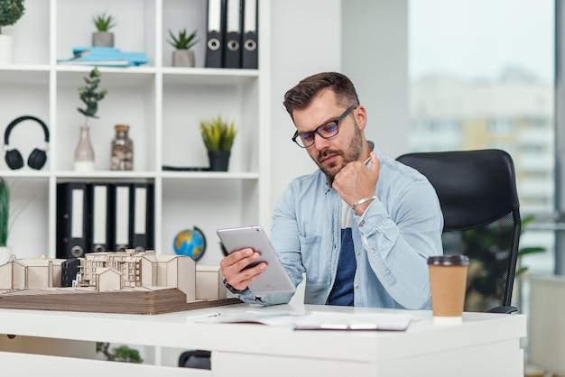 Опытный архитектор-мужчина в офисе осматривает проект жилого комплекса и производит расчеты с помощью планшетного компьютера.