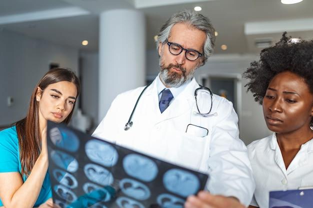 Опытный врач-мужчина помогает своим коллегам с интерпретацией рентгеновского снимка легких.