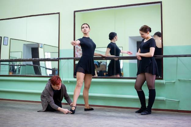 女の子ダンサーを助ける振り付けのレッスンを持っている経験豊富な男性教師