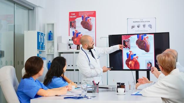 経験豊富な男性医師が、会議室でモニターを指差しながら、心臓の問題の画像を検証された同僚と一緒に分析します。患者の治療に関する診断について話し合う医師