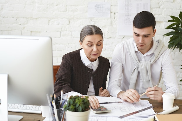 Experienced mature woman architect with gray hair sitting at her workplace with young focused man assistant revising drawings and project documentation, using calculator to check measurements