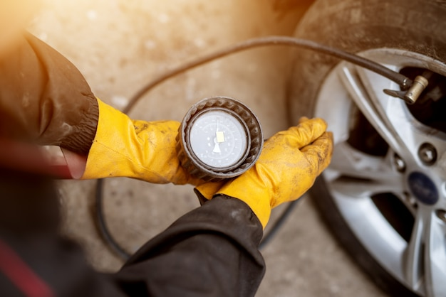 An experienced mechanic in orange gloves is precisely filling air and adjusting its pressure in a car wheel.