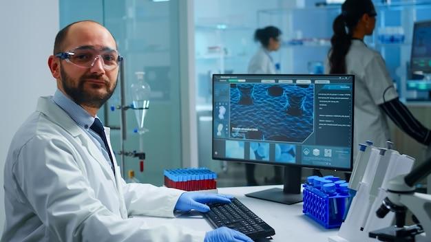 経験豊富な医療ラボの開業医が笑顔でカメラを見ています。科学研究、ワクチンのためのハイテクおよび化学ツールを使用してウイルスの進化を調べる科学者医師のチーム