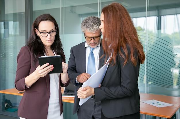 Partner esperti in piedi nella stanza dell'ufficio