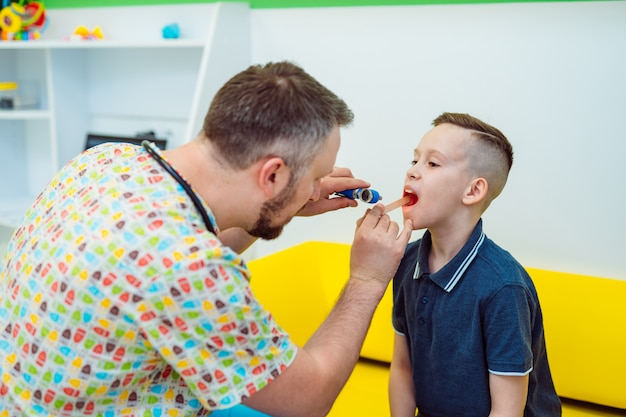 Experienced physician is looking at boy's throat with special instruments in clinic. pediatrician in medical uniform examining throat little child.