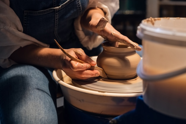 An experienced potter a girl in an art studio makes a pot of clay with her hands.
