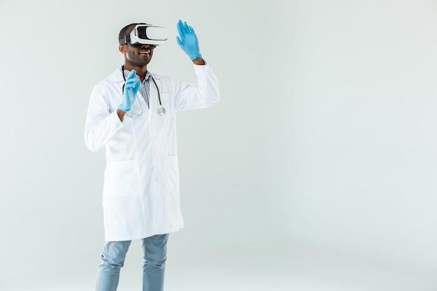 Опытный профессиональный врач в очках vr, стоя у белой стены