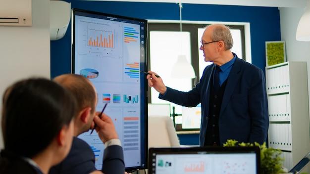 디지털 장치를 사용하여 브레인스토밍 룸에서 비즈니스 회의 중 재무 프레젠테이션을 분석하는 경험 많은 프로젝트 리더. 나 동안 전문 스타트업 회사에서 일하는 다민족 팀