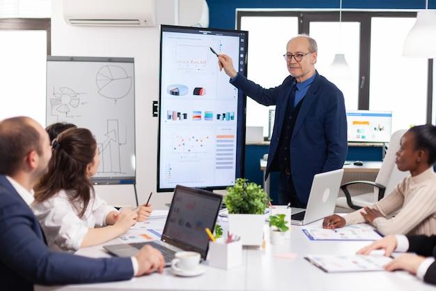 デジタルデバイスを使用してブレーンストーミングルームでのビジネス会議中に財務プレゼンテーションを分析する経験豊富なプロジェクトリーダー