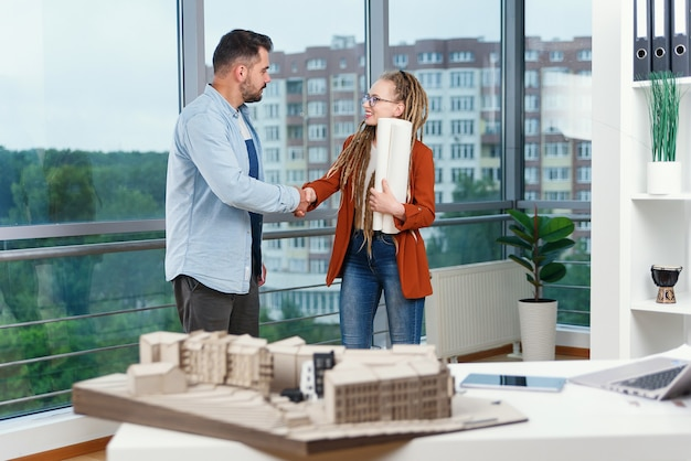 Опытные довольные дизайнеры обсуждают детали проекта, используя план здания и