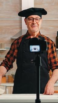 キッチンでの調理に関する経験豊富なシニアシェフのレコーディングチュートリアル。ソーシャルメディアでの撮影ブログをデジタル機器と通信するインターネット技術を使用する引退したブロガーインフルエンサー