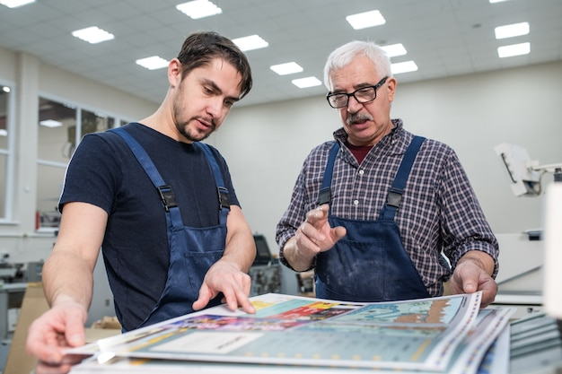 Experienced senior worker in glasses explaining young man how to estimate print quality during his internship
