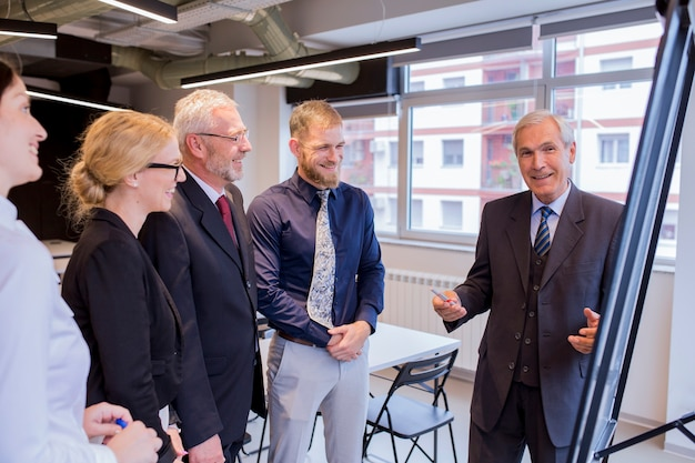 Experienced smiling businessman giving presentation to executive team